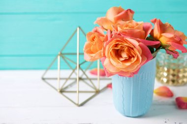 Bunch of fresh orange roses in blue cup on white wooden background against  turquoise  wall. Place for text. Floral still life.