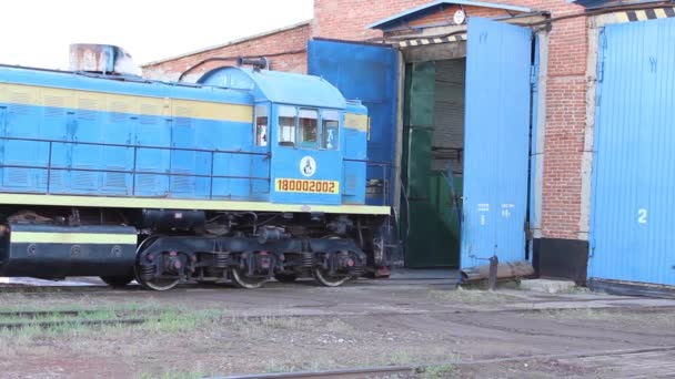 An old blue diesel locomotive calls into the repair shop.