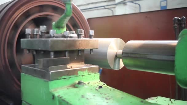 A metal round billet rotates in a lathe and is machined by a turning tool.