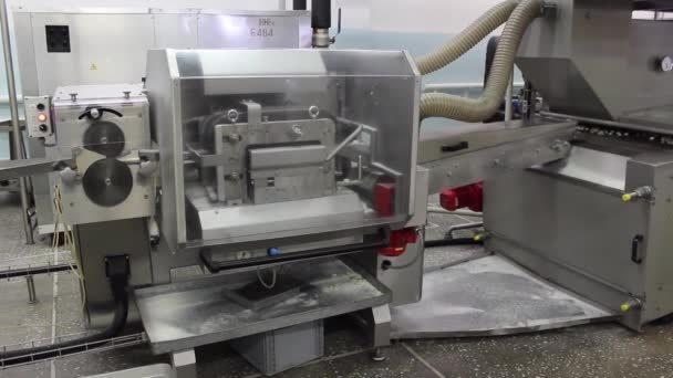 The machine throws caramel candies on a conveyor belt on an automatic line in a confectionery factory.
