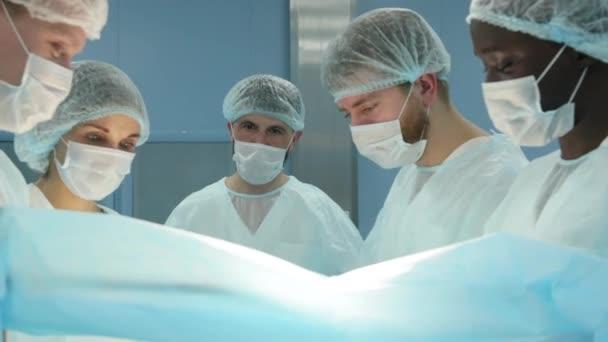 Der leitende Chirurg im Operationssaal, wo der Patient auf ihn wartet, und er beginnt mit der Operation. Echt modernes Krankenhaus mit authentischer Ausstattung.