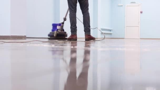 čistič myje molo s profesionálním leštičem. Úklid podlahy v hale kancelářské budovy
