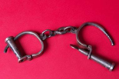 Vintage handcuffs on a scarlet background.