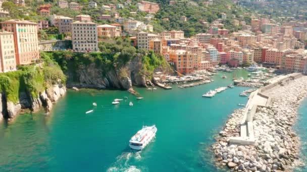 Ein kleines Kreuzfahrtschiff fährt in den Hafen von Camogli in der Nähe von Genua, Italien. Ein Motorboot kommt an Buhne und Leuchtturm vorbei zurück in die Marina.