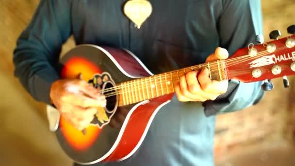 Detailní záběr na muže hrajícího na kytaru v Ludhianě, Paňdžáb, Indie