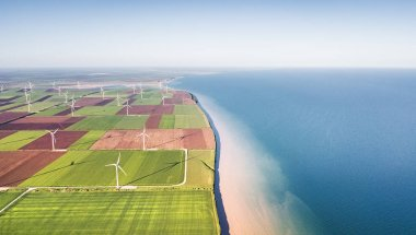 Wind power station on the field near sea. Concept and idea of alternative energy development