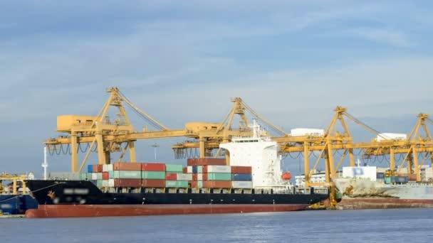 Időközű ipari konténer szállítási teherhajó a működő daru híd hajógyár alkonyatkor a logisztikai importálása és exportálása