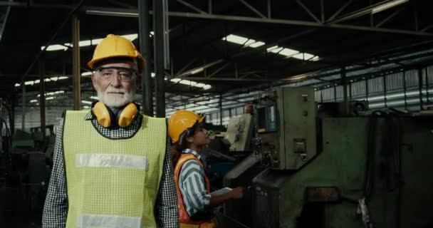 Worker in factory crossing arm and thump up in front of the machine