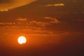 Slunce na obloze s mraky při západu slunce.