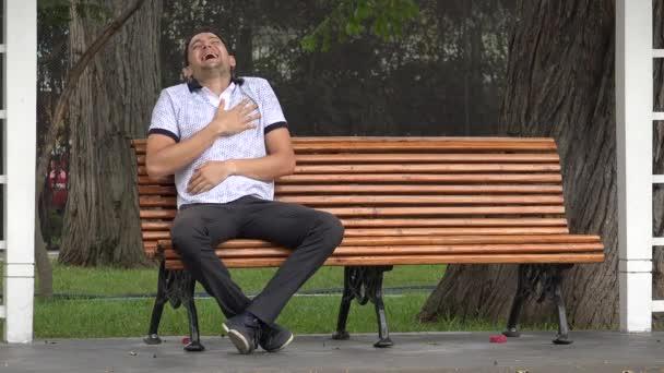 Mann lacht allein auf Parkbank sitzend