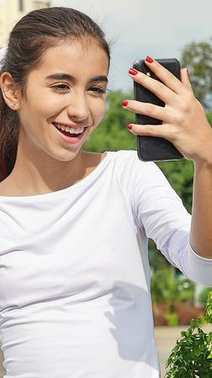 Beautiful Teenage Female Using Cell Phone And Happy