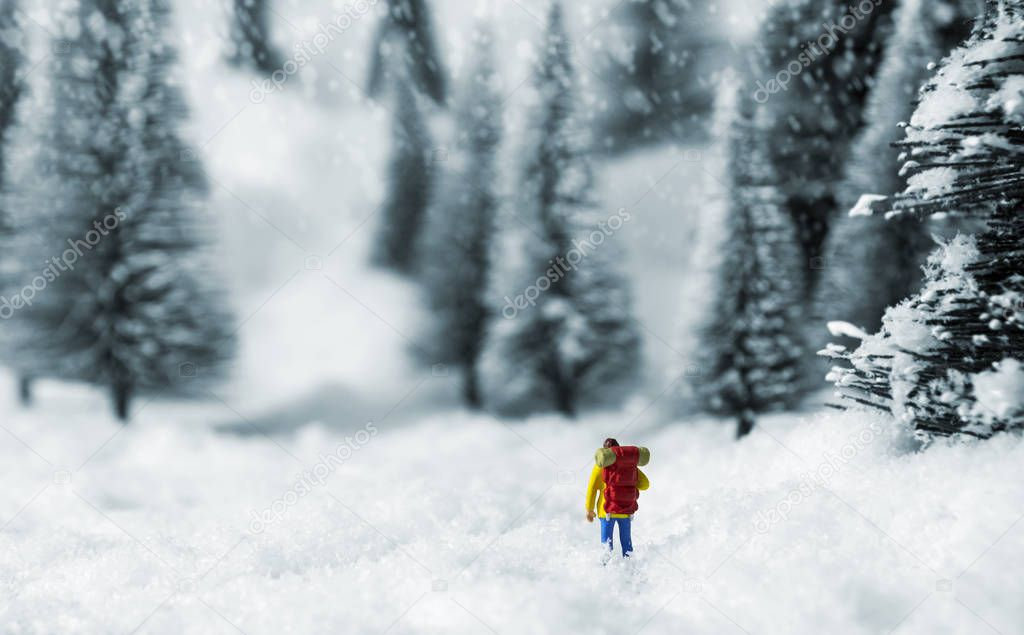 Miniature backpacker walking in pine forest during winter