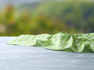 Empty wooden table with green tablecloth