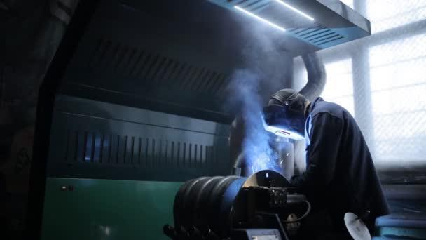 Schweißer in einem Schutzhelm arbeitet an einem Industrieunternehmen