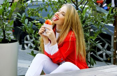 young woman licking donut