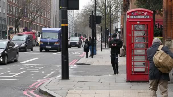 LONDON - MARCH 19, 2020: A man wearing a PPE face mask and using a smartphone while looking lost next to a traditional, red British telephone box