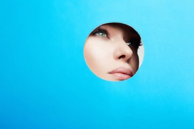 Beautiful young woman in circle hole with color paper
