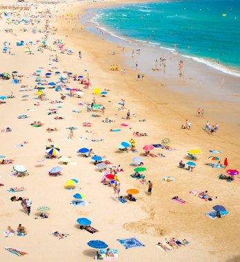 Portimao, Algarve, Portugal, June 19, 2017: Praia de Rocha beach with tourists and colourful umbrellas