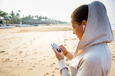 Young woman is listening to the music on the phone before joggin