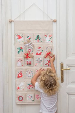 The boy opens a gift from the advent calendar