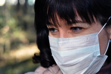 Portrait of a sexy woman with blue eyes and long hair in a medical mask on the street. Girl in a medical mask against viruses and infections. The concept of coronavirus covid-19.
