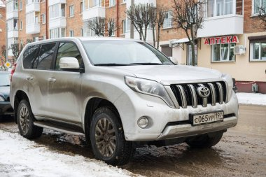 Toyota Land Cruiser parked in winter on a dirty russian road.