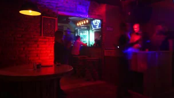 Dj plays in modern night club  illuminated by colorful light.