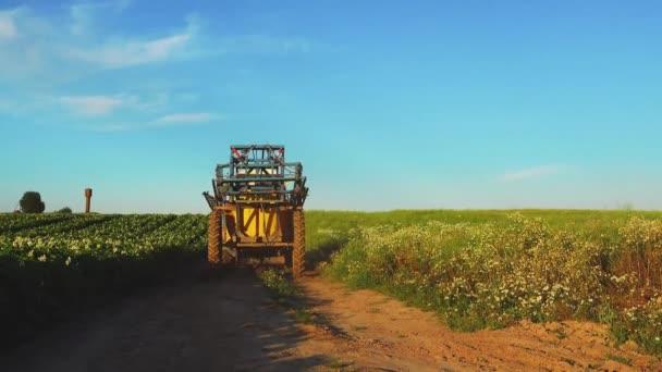 Zemědělský traktor v obdělávaném poli, jeřáb natáčení