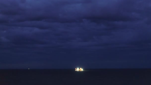 Timelapse. Night in ocean and storm clouds, fishing ships in the distance.