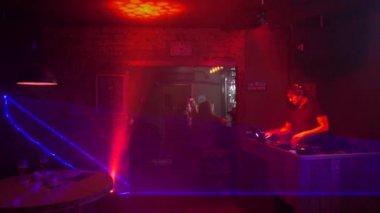 Dj plays in modern night club. Beautiful light effects.