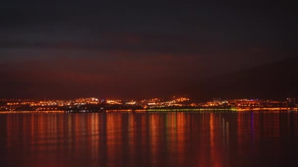Timelapse. Beautiful evening sky over night city and sea.