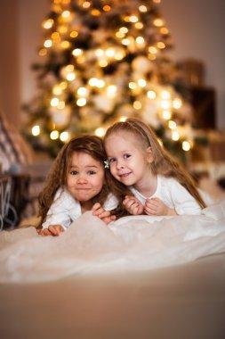 happy girls sister   background of golden bokeh Christmas lights
