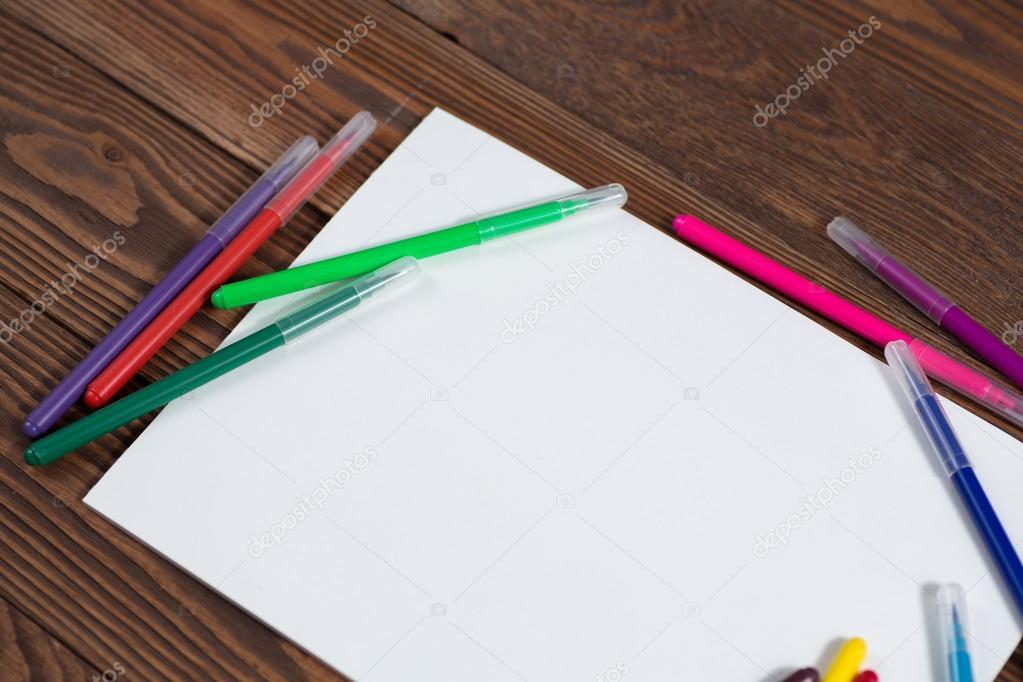 Crayones de colores y una hoja de papel madera de notebook — Fotos ...