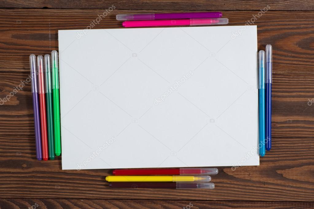 Crayones de colores y una hoja de papel madera de notebook — Foto de ...