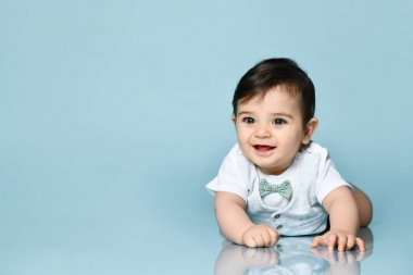 Little toddler in white bodysuit as a vest with bow-tie, barefoot. He is laying on the floor against blue background. Close up