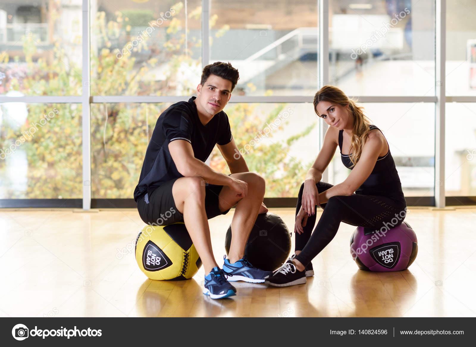 4a171ced4f40 Uomo e donna che si siede con fitballs in palestra. Giovani vestiti  abbigliamento sportivo. — Foto di javiindy