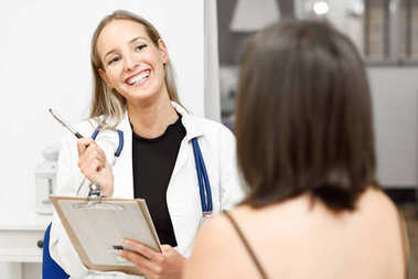 Female doctor explaining diagnosis to her young woman patient.
