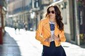 Fotografia Giovane donna bruna con gli occhiali da sole nel fondo urbano