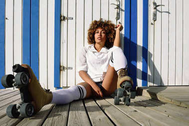 Young black woman on roller skates sitting near a beach hut.