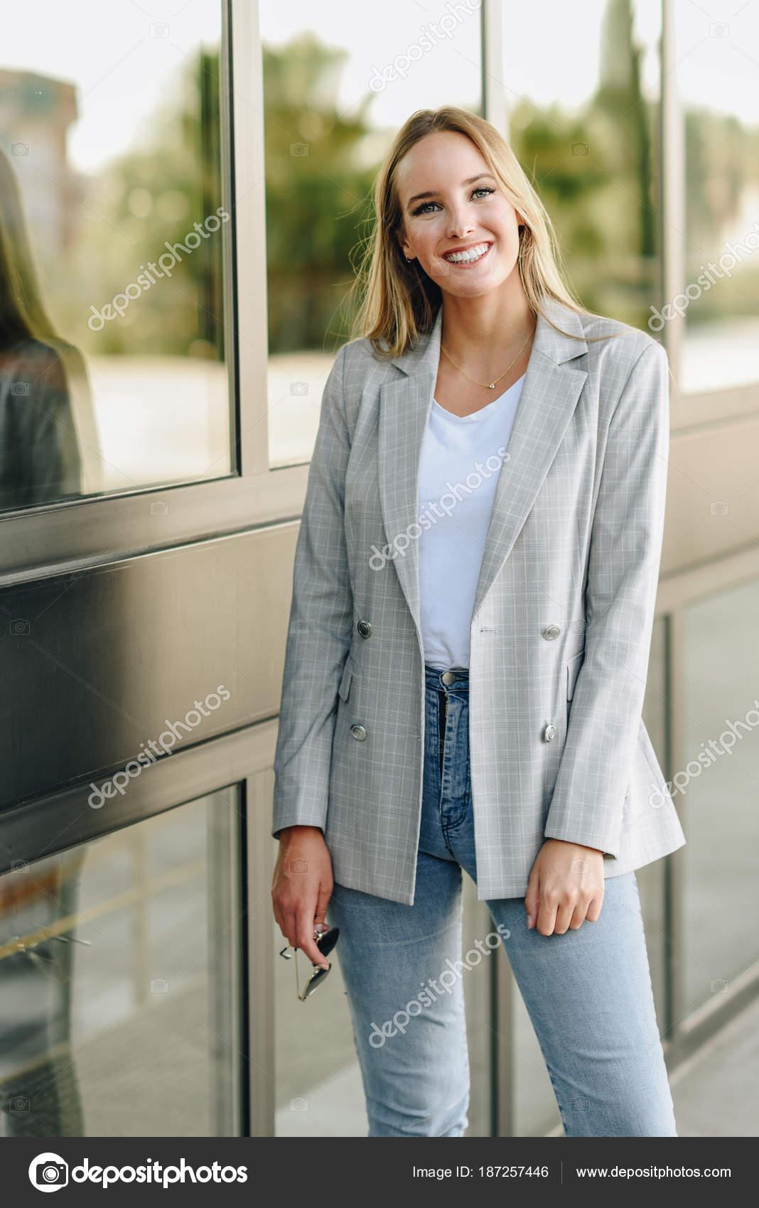 1e8d106dd Hermosa mujer caucásica joven sonriendo en el fondo urbano. Chica rubia con ropa  casual en la calle. Mujer con chaqueta elegante y jeans azul — Foto de ...