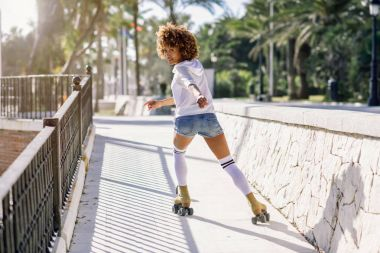 Black woman, afro hairstyle, on roller skates riding near the be