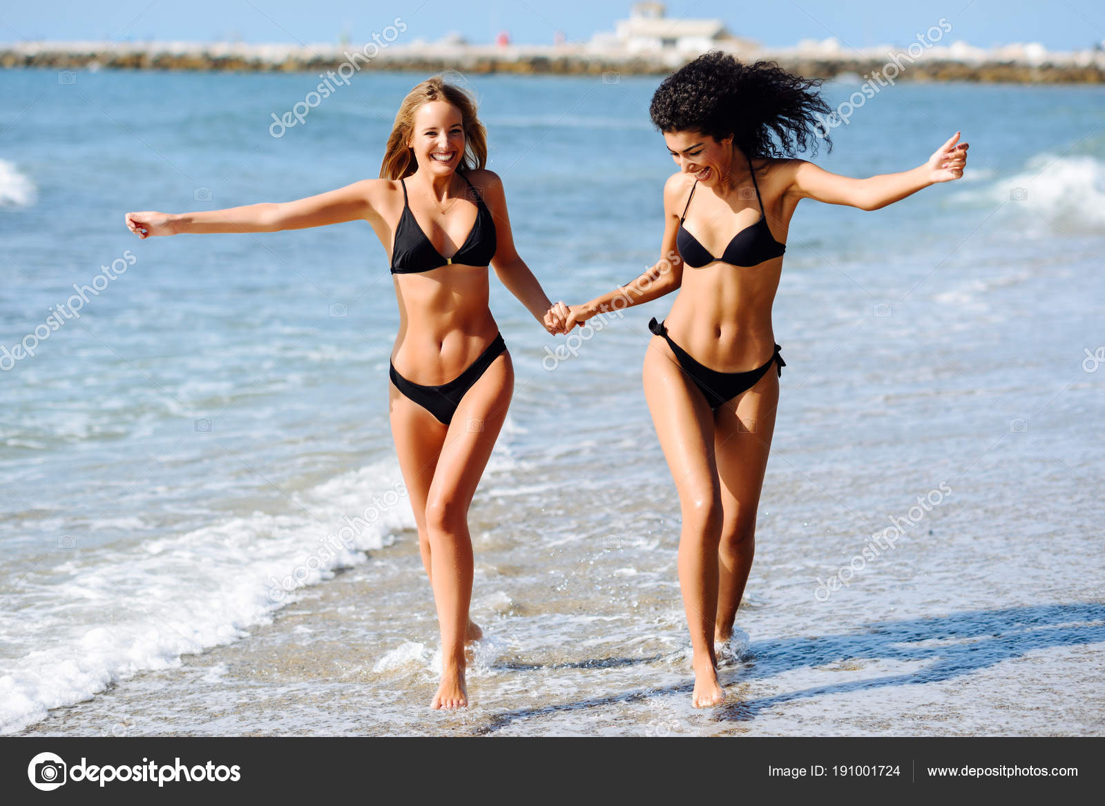 ca2a75414b993 Two young women with beautiful bodies in swimwear on a tropical beach. Funny  caucasian and arabic females wearing black bikini walking along the shore  ...