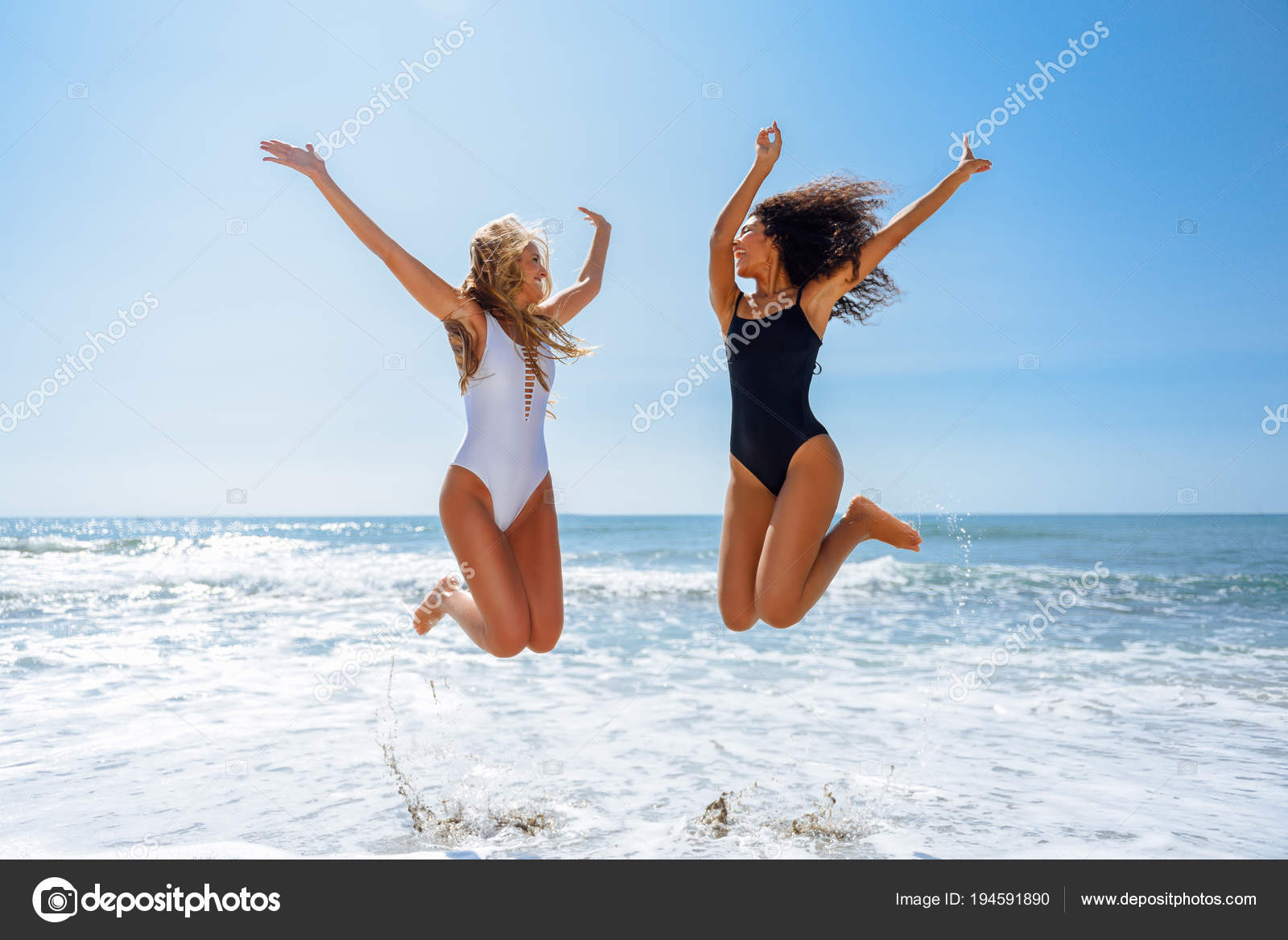 4e9f6f993e88b Two funny girls in swimsuit jumping on a tropical beach — Stock Photo