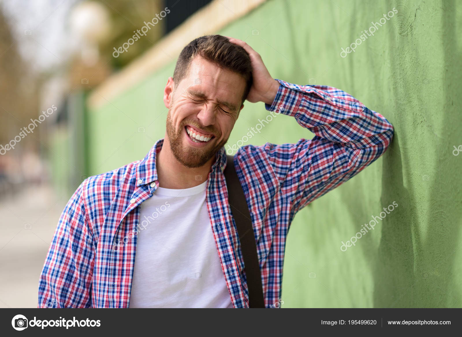 7cd47a4b Attractive young man laughing outdoors. Funny guy wearing casual clothes in  urban background. Lifestyle concept.