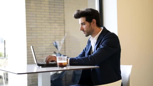 Businessman sitting in cafe, drinking fresh coffee typing with his laptop.