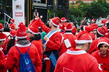 Madrid, Spain, December 8th 2019: Crowd of Santa Clauses running in street