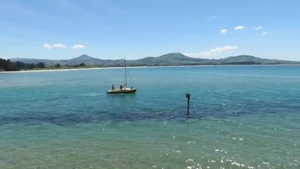 Egy hajó vitorlázik Karitane Beach-en, Dunedin, South Island-en.