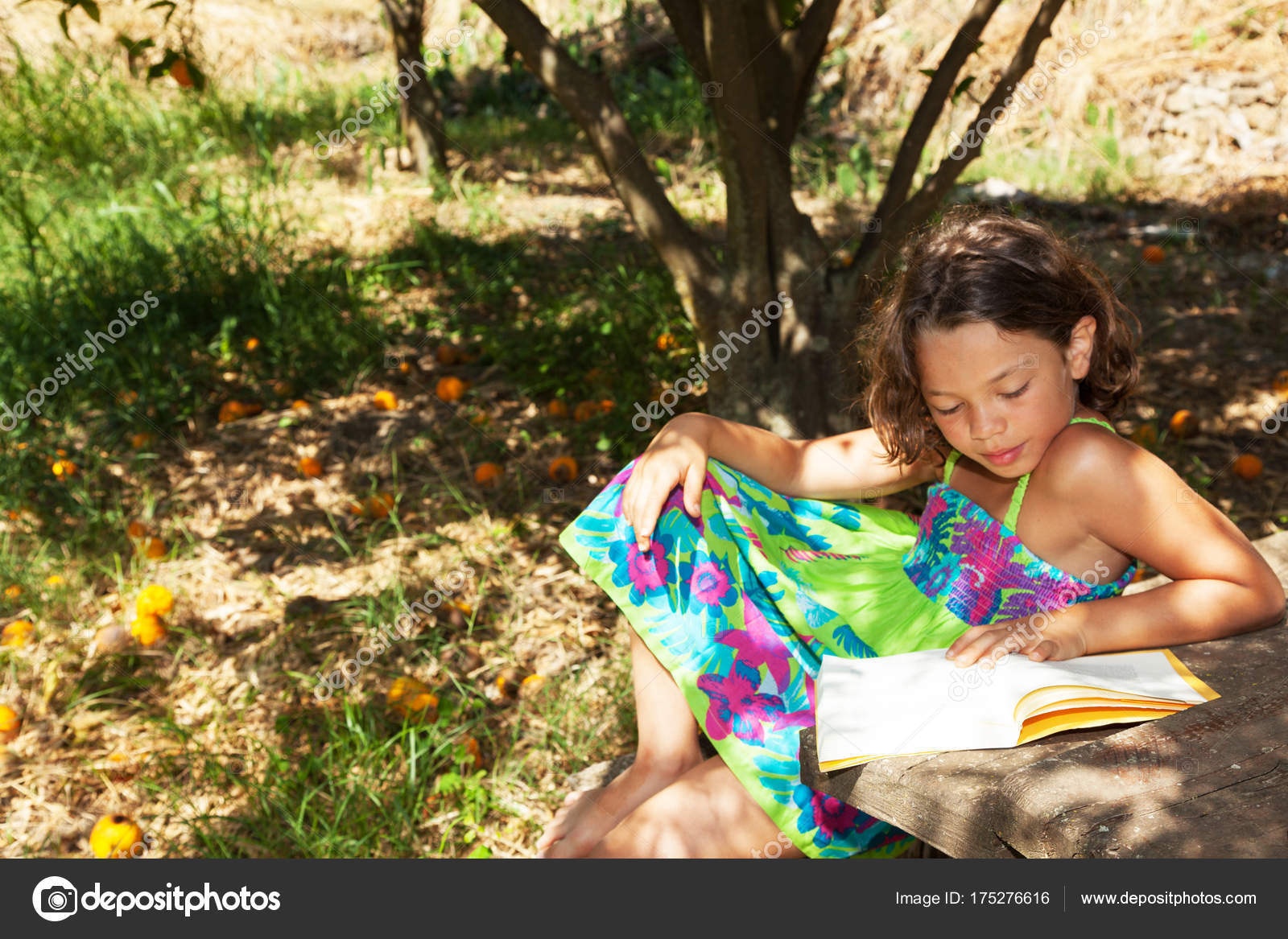 a beautiful little girl reading a yellow book in the garden with ...