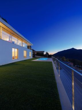 Modern villa, exterior in the night, lights on
