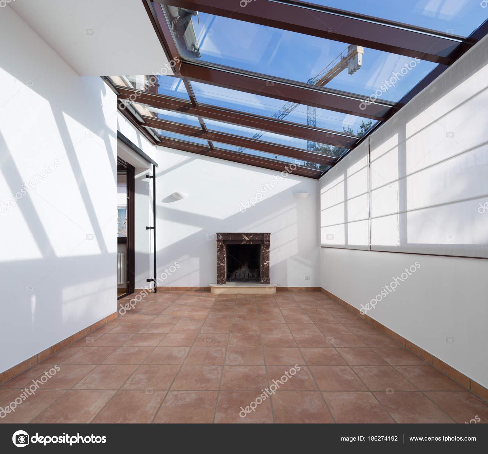 Non arredato camera con grandi finestre sul soffitto e caminetto ...